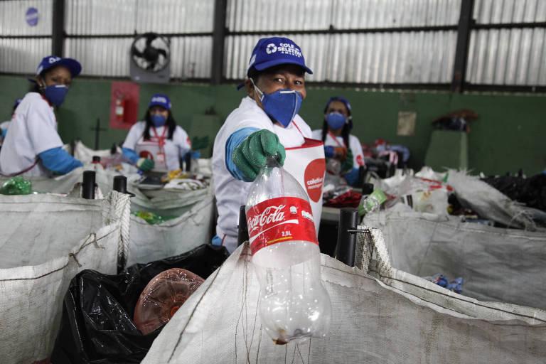 Funcionária de máscara e luvas segura garrafa vazia de coca-cola dois litros