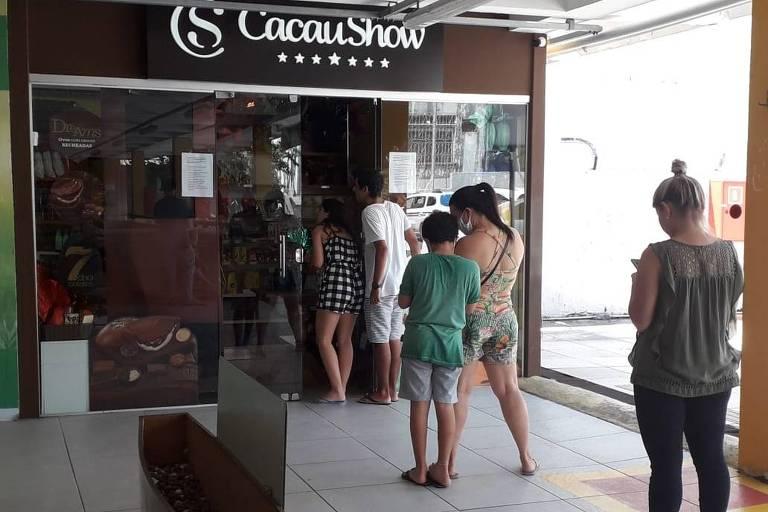 Pessoas distantes umas das outras fazem fila na porta da Cacau Show