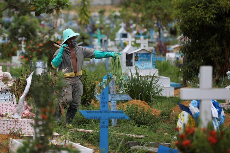 Em meio a lápides, cruzes coloridas e plantas, homem negro de macacão cinza, chapéu e luvas verdes aponta ao longe enquanto segura uma pá com a outra mão