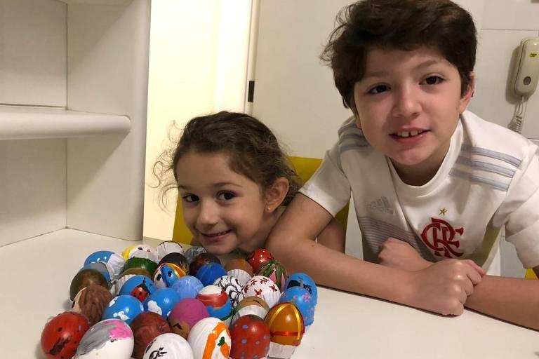 Os irmãos Clarissa, 5, e Thales Gennari de Assis, 9, de São Paulo, com as casquinas de ovos que pintaram para presentear amigos e familiares quando a quarentena acabar