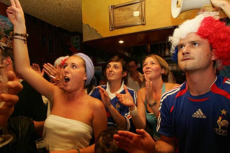 Torcedores assistem a partida de futebol em bar