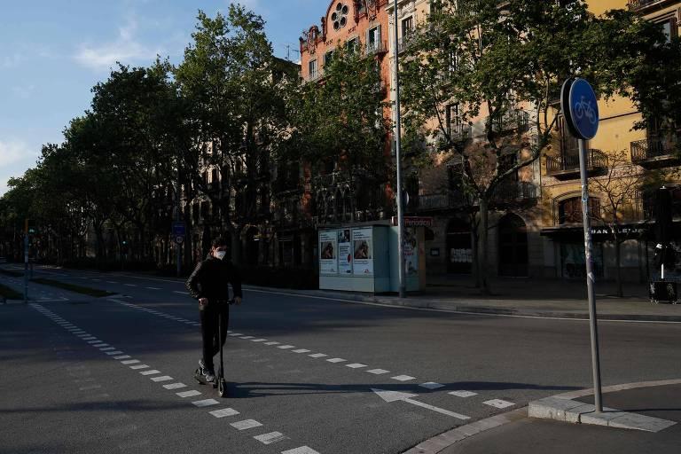 Um homem com máscara de proteção no rosto anda de patinete em rua deserta de Barcelona, na Espanha