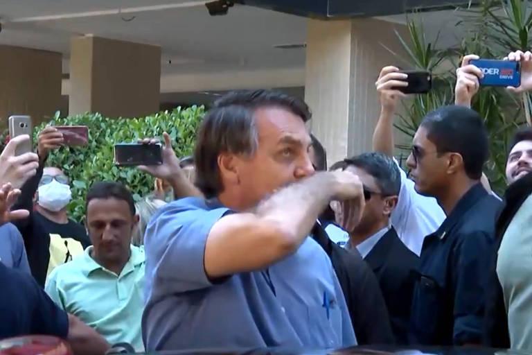 O presidente Jair Bolsonaro limpa o nariz e depois cumprimenta apoiadores em Brasília