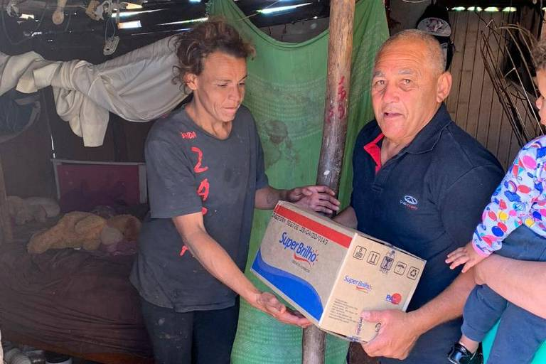 Voluntários distribuem cesta básica para Rosângela da Silva, em Parelheiros