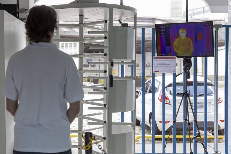 Funcionário passa por câmara térmica que detecta zonas de calor do corpo em entrada da fábrica da Unilever em Valinhos (SP)