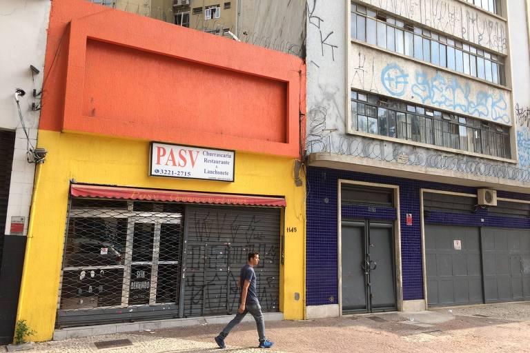 Homem passa em frente a fachada laranja e amarela de sobrado com cartaz branco escrito Pasv