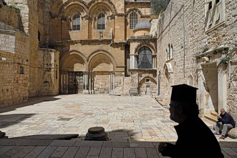 Um padre anda perto da entrada da Igreja do Santo Sepulcro, na antiga Jerusalém, durante a pandemia da Covid-19