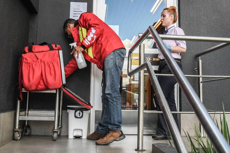 Vendas online se tornaram maioria após a pandemia; na foto, motoboy precisa limpar sua mochila de entrega antes de entrar na loja para buscar o produto