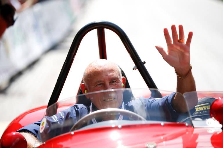 Stirling Moss acena com  a mão esquerda de dentro de um carro de corrida vermelho