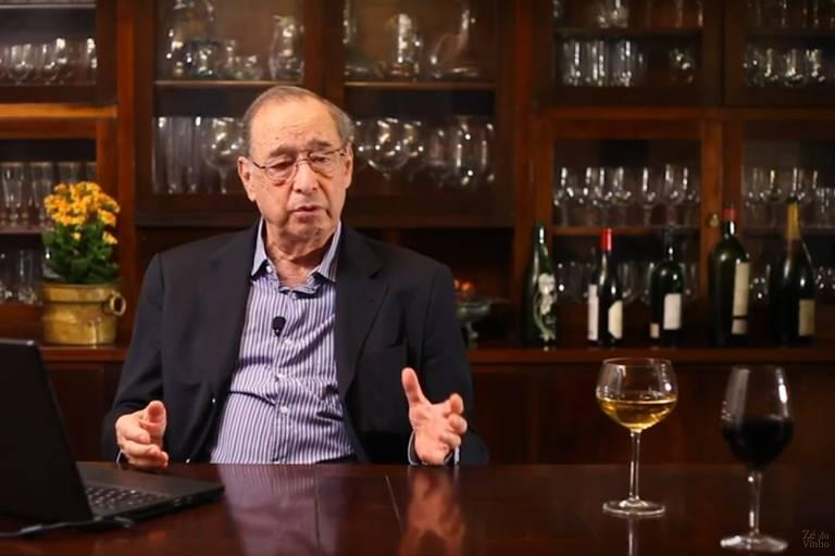 Imagem de José Ruy Sampaio, de paletó e camisa social, com adega ao fundo e duas taças de vinho sobre a mesa