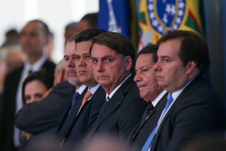O presidente Jair Bolsonaro (centro) e o presidente da Câmara, Rodrigo Maia (à dir.), entre outras autoridades, durante solenidade no Palácio do Planalto