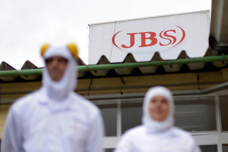 Trabalhadores são vistos em uma fábrica da JBS no Paraná. Eles vestem roupas especiais