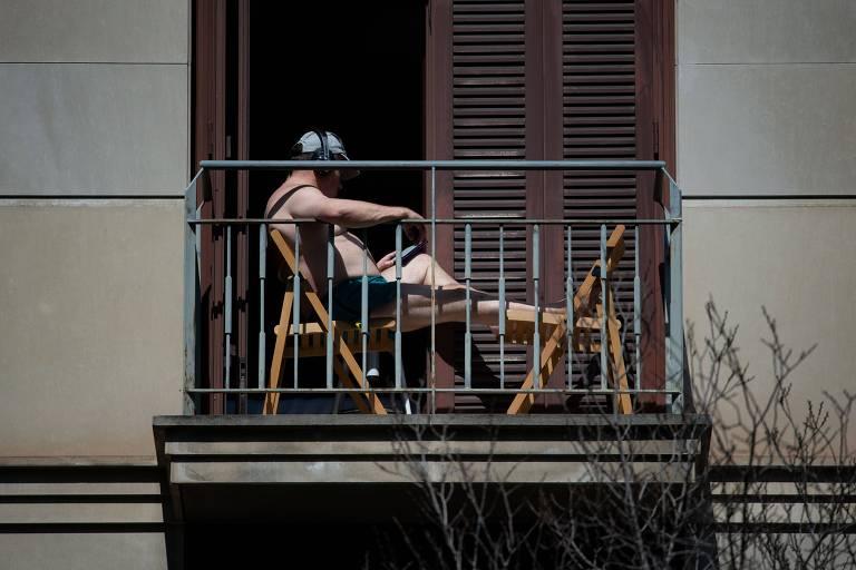 Homem toma sol em varanda de apartamento em Barcelona