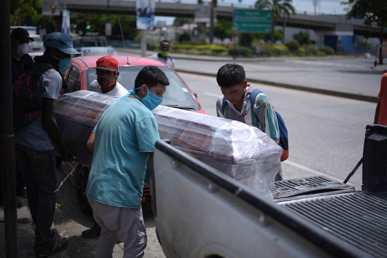 Funcionários colocam caixão em picape para levá-lo a cemitério de Guayaquil