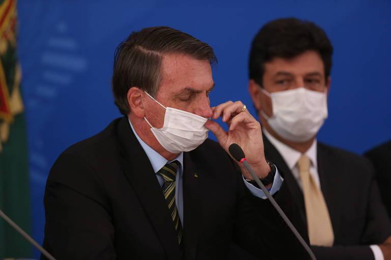 O presidente Jair Bolsonaro mexe em máscara durante entrevista para falar sobre o coronavirus, em março