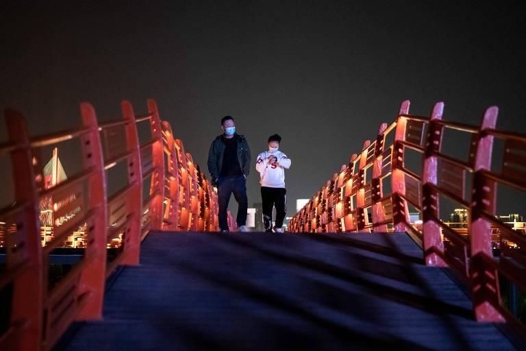 Pessoas com máscara atravessam ponte em Wuhan; restrições na cidade estão acabando