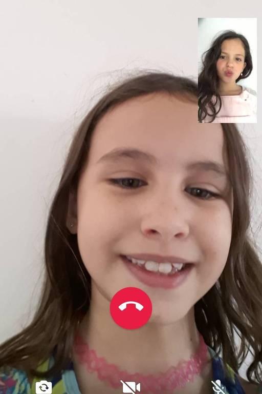 Gabriela está sorrindo para a câmera do celular e a imagem de Iara também sorrindo está no topo da tela