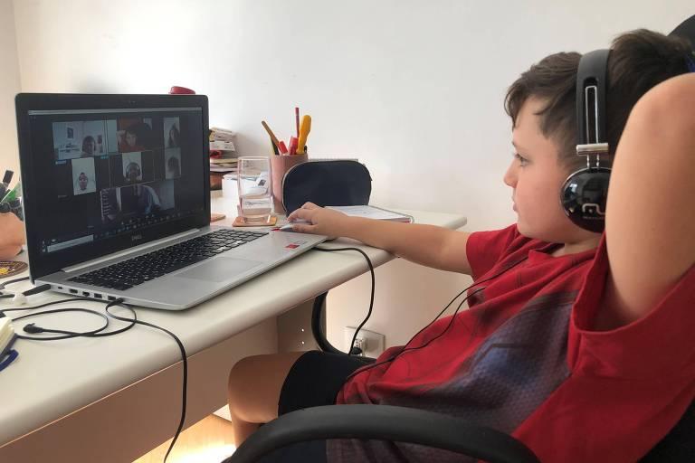 Rafael está com fones de ouvido na frente do computador vendo seus amigos em uma videoconferência