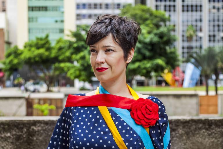 Kiara está de blusa azul no centro da cidade, com uma faixa vermelha nos ombros, em uma praça urbana