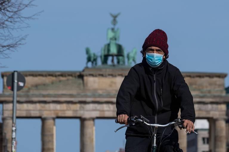 Homem de máscara passa de bicicleta diante do Portão de Brandenburgo, em Berlim