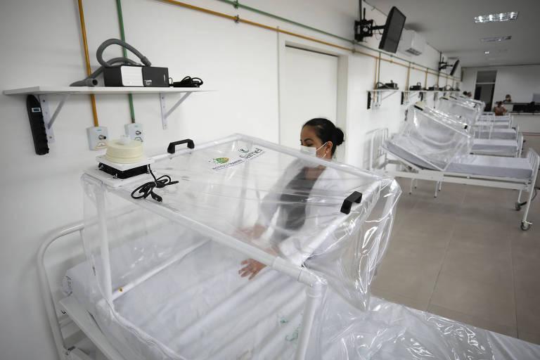 Funcionária prepara leito de UTI no hospital de campanha de Manaus; vemos o leito em primeiro plano, com outros mais ao fundo; sobre o leito há uma cápsula de ventilação feita com tubos de PVC e plástico transparente