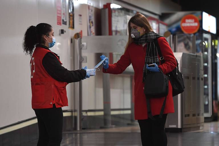 Voluntária da Cruz Vermelha distribui máscaras em estação de metrô em Madri