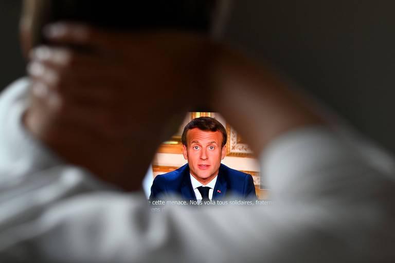 Espectador assiste a pronunciamento do presidente francês, Emmanuel Macron, a partir do Palácio do Eliseu