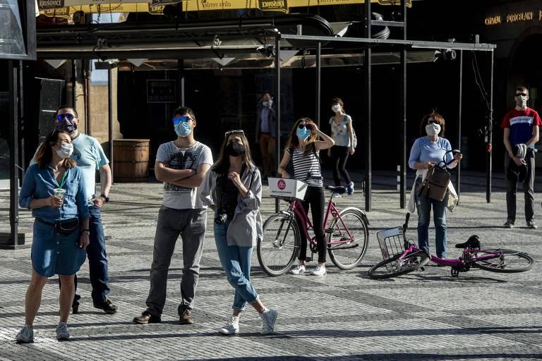 Pessoas com máscaras observam relógio em Praga, capital da República Tcheca