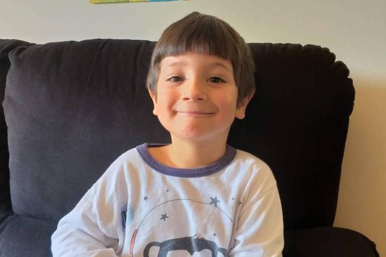 Vitor está de pijama no sofá e sorri