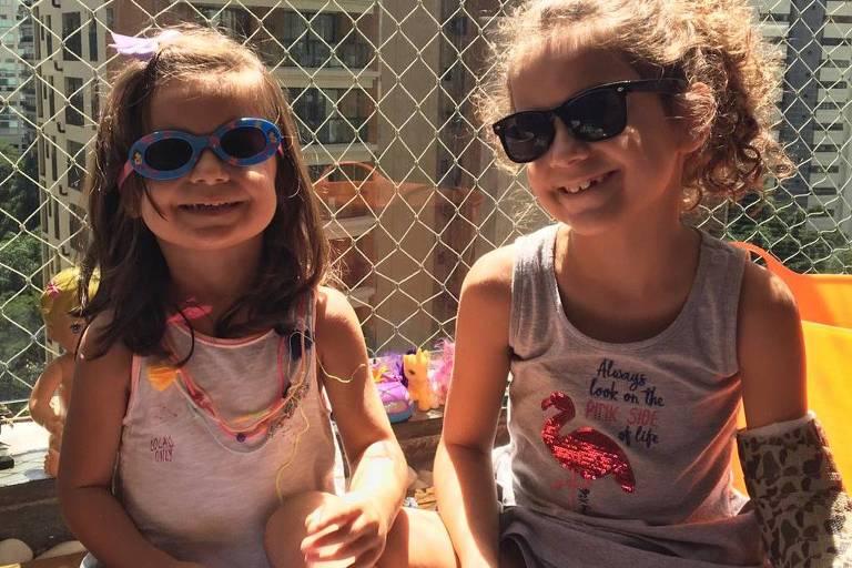 Isabela e Marina estão de óculos escuros sentadas em uma rede na varanda