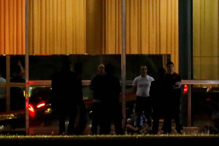 Presidente Jair Bolsonaro, cercado por seguranças, sentado no chão em frente ao Palácio da Alvorada, nesta segunda (13)
