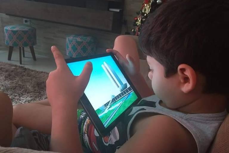 Vitor Piconi, 7, com autismo, usa um tablet