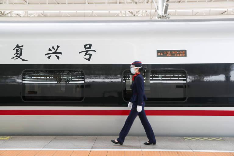 Funcionária com máscara e luvas em estação de trem em Xangai