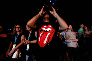 A concertgoer uses binoculars while watching a performance by The Rolling Stones during Desert Trip music festival at Empire Polo Club in Indio