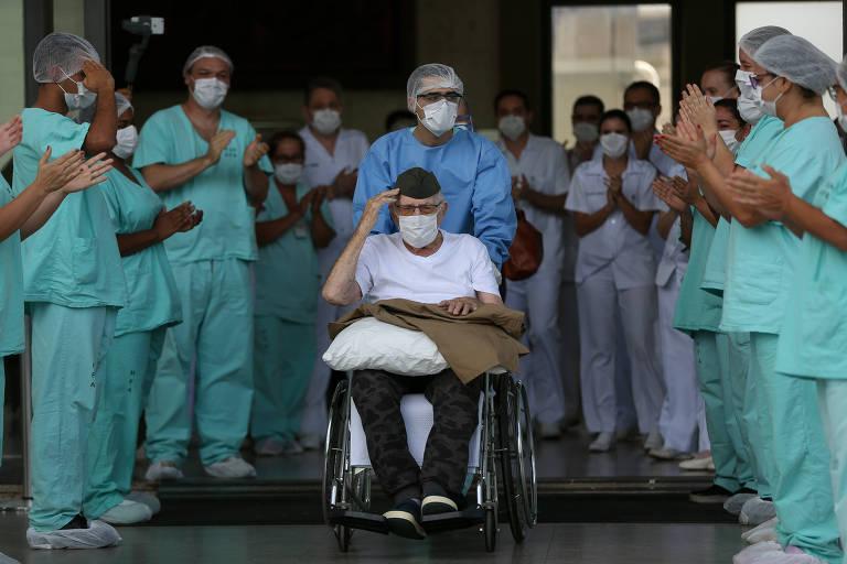 Ermando Armelino Piveta, 99, é aplaudido pela equipe médica e bate continência ao deixar hospital em Brasília