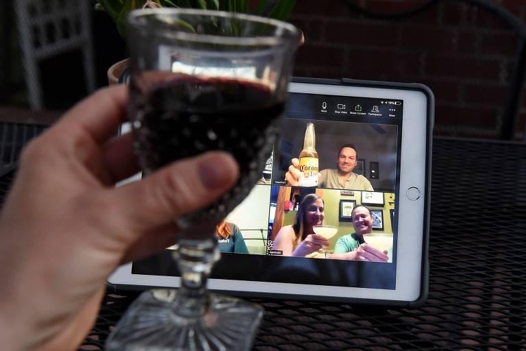 Mulher ergue copo de vinho em happy hour virtual com amigos nos EUA durante pandemia de coronavírus; ao fundo, tela em que os amigos aparecem bebendo
