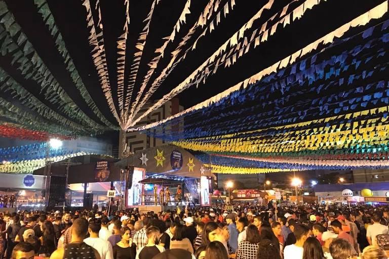 Multidão em pátio coberto por fitas com bandeiras coloridas
