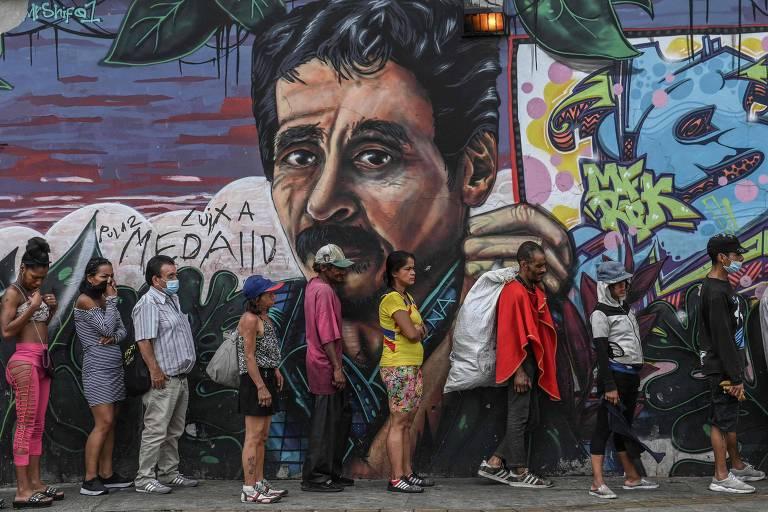 Moradores de rua aguardam para receber comida de um abrigo de Medellín, na Colômbia