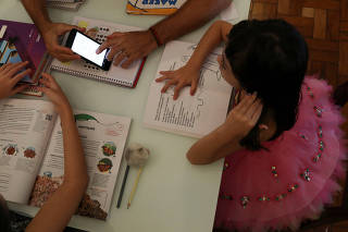 Alice, 5, watches a video sent by school as she studies at home with her father Rodrigo Pinto as his work was suspended during a lockdown imposed by the state government because of the coronavirus disease (COVID-19) outbreak in Santo Andre