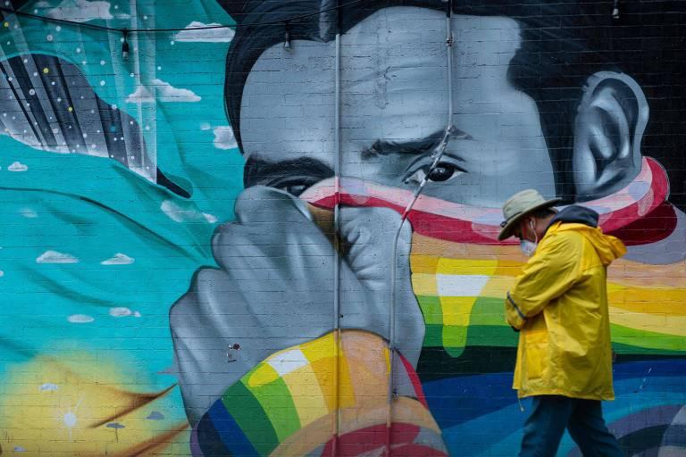 Homem com máscara caminha em frente a mural na cidade de Nova York