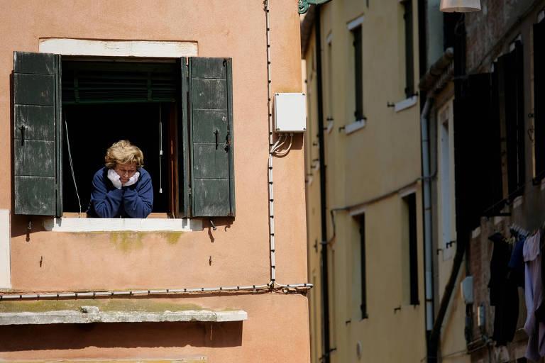 mulher loira de cabelos curtos, casaco azul e luvas de plástico olha por uma janela. O prédio é marrom claro e as janelas são de madeira e cinza escuro. Ela tem um olhar triste.