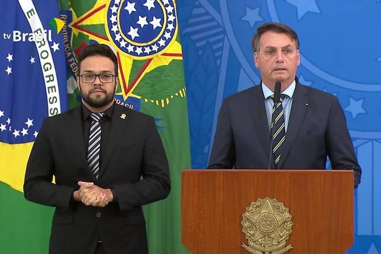 O presidente Jair Bolsonaro, ao lado de um intérprete de Libras, anuncia Teich no ministério