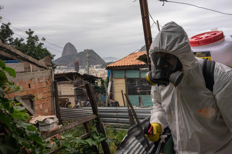 Os irmãos Thiago e Tandy Firmino fazem limpeza com quaternário de amônio em vielas do morro Santa Marta, em Botafogo, na zona sul do Rio; ao fundo, o Pão de Açúcar