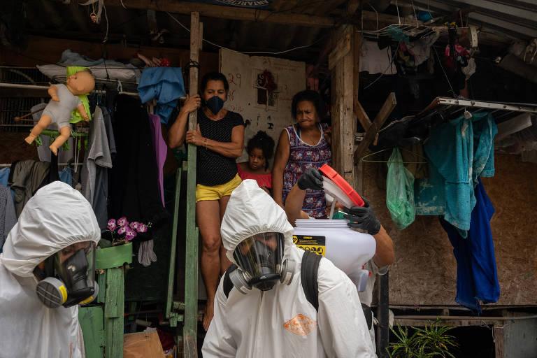 Os irmãos Thiago e Tandy Firmino fazem limpeza com quaternário de amônio em vielas do morro Santa Marta, em Botafogo, na zona sul do Rio; atrás deles, moradores os observam