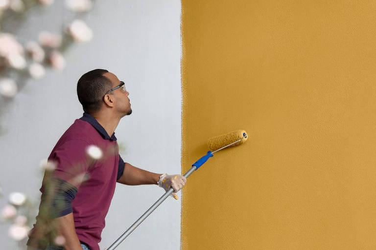 Pintor usa rolo em parede amarela