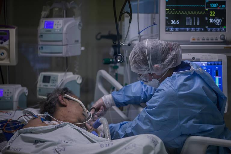 Enfermeira do Instituto de Infectologia Emilio Ribas medica paciente na UTI do hospital, que está toda dedicada a pacientes de Covid-19