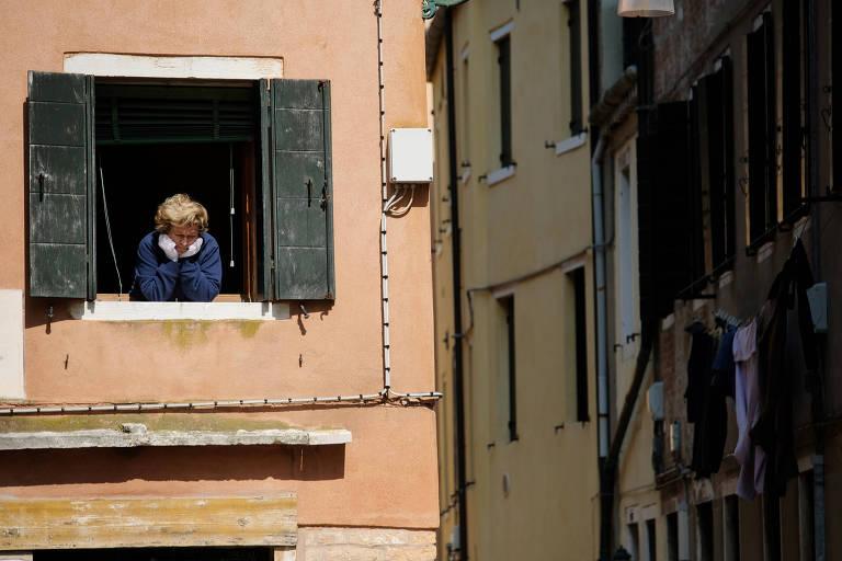 Mulher olha pela janela durante o confinamento em Veneza, na Itália