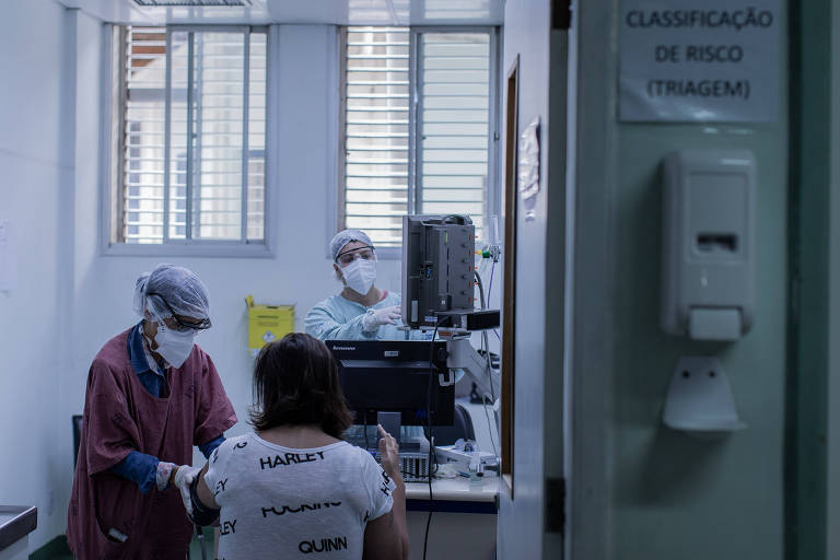 Equipe médica realiza a triagem de pacientes que podem estar infectados pelo coronavírus; a foto, tirada de fora da sala de triagem, mostra duas atendentes paramentadas com toucas, óculos, máscaras e outros equipamentos medindo sinais vitais de uma mulher, de costas