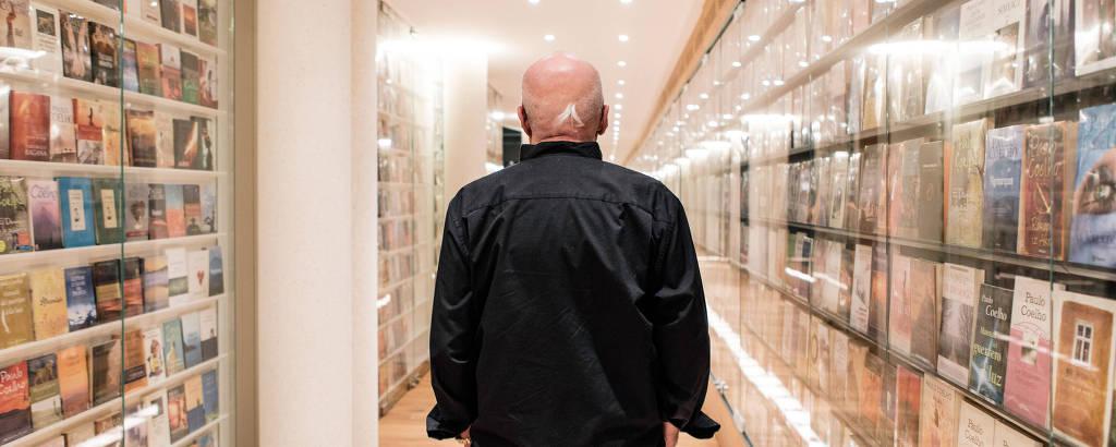 Paulo Coelho de costas em um corredor com estantes de livros nas laterais