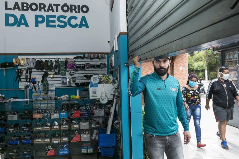 Homem de camiseta azul descendo porta de metal de loja com produtos de pesca
